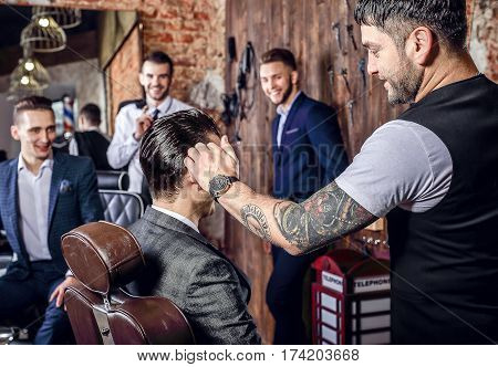 Master makes hair style in barbershop salon. Close up photo.