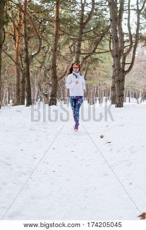 Sport Young Woman Running In The Winter Forest.