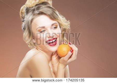 Sexy Playful Caucasian Blond Girl with One Orange Fruit in Hands. Posing Against Color Background. Horizontal Image Composition