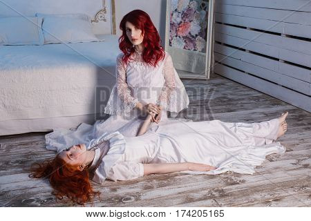 Two beautiful girls with red hair in a beautiful white wedding Victorian dresses. Female victorian style. The fragile girl. Thin waist. A victorian woman sits on a chair. Conceptual photography. Girl lies on the floor