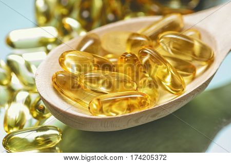 Closeup fish oil dietary supplement. Wooden spoon of oil fish capsules. Omega 3 pills fish oil capsules.