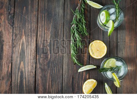 Alcoholic drink gin tonic cocktail with lemon rosemary and ice on rustic wooden table copy space.