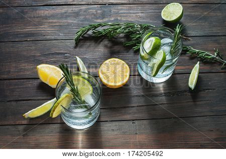 Alcoholic drink gin tonic cocktail with lemon rosemary and ice on rustic wooden table.
