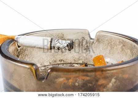 Close up of cigarette in ashtray on white background
