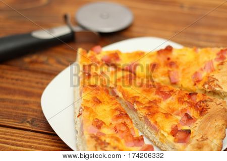 Pizza on plate with cutter on wood table