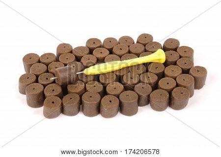 Yellow stinger needle and brown pre-drilled halibut pellets for carp fishing isolated on white background with soft shadow