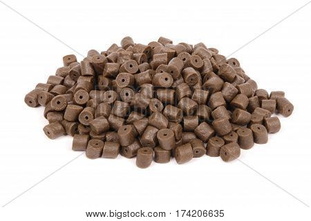 Brown pre-drilled halibut pellets for carp fishing isolated on white background with soft shadow