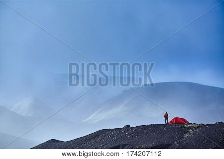 Travel to Iceland. Beautiful Icelandic landscape with mountains, sky and clouds. Trekking in national park Landmannalaugar. Morning in Camping . Tents and hikers in the camping. Travel concept.