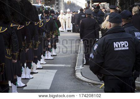 NEW YORK - JAN 13 2017: NYPD Det. Steven McDonald funeral procession and service at St Patricks Cathedral, 5th Avenue, Manhattan - Law enforcement personnel and members of clergy line up on Fifth Ave.