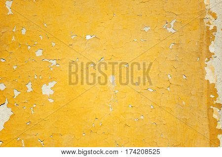 Fragment of cracked peeling yellow painted stone wall
