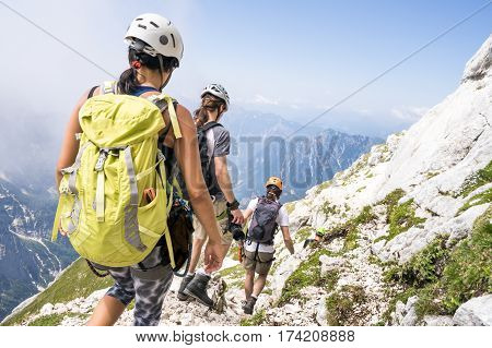Active young tourists on holiday in Alps, sporting hikers in mountains, group of tourists on  trip around mountains, friends on trip in mountains of Europe