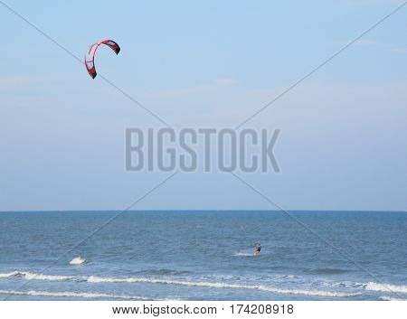 Kiteboarding on the blue sea and under blue sky of Thailand