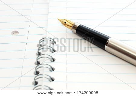A gold-nibbed pen on a spiral-bound notepad
