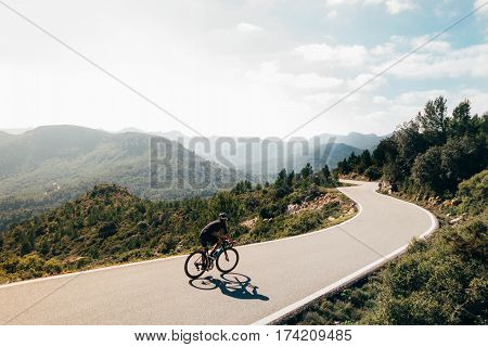 Male cyclist descending a swinging mountain road