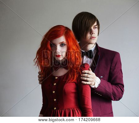 Couple on a white background. Informal guy with long hair in a jacket and a woman with long red curly hair in a red dress with bow tie on the neck on a white background holding hands. Red-haired girl with pale skin and blue eyes. Stylish couple. Couple in