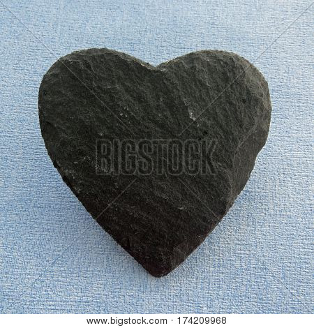 Black Slate heart shape on a blue background with room for text on the slate