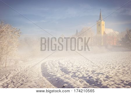 Old Croatian church in Hungary covered by fog