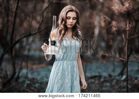 Very cute young lost girl with a kerosene lamp. Doll appearance. Lost woman with brown hair in a turquoise dress on nature with lamp. Long hair. Natural light. Model posing on the nature with lamp. Lamp in hand. Lost in forest