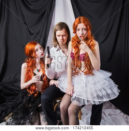 A man gangster with long hair in a white shirt sits on a chair. Gangster with a gun on a black and white background. Two young red-haired girl with long hair with lollipops in hands in underwear and stockings with gangster with gun. Killer with two girls