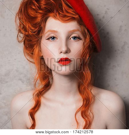 A vintage woman with red hair in a red dress. Red-haired vintage girl with pale skin and blue eyes with a bright unusual appearance with vintage beret on her head on a gray background. French courtesan. Vintage photo