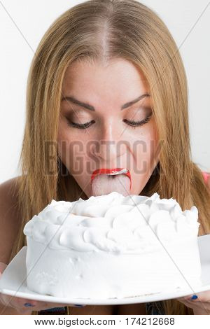 Busty sexy girl eating cake with whipped cream. white background