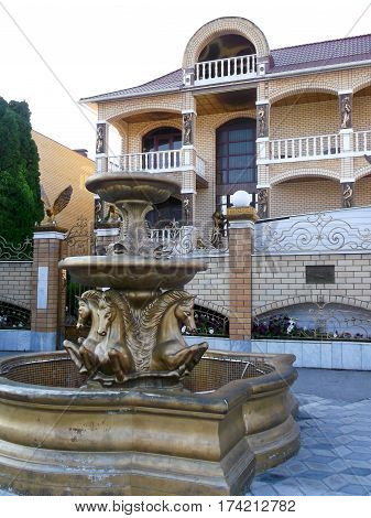 a beautiful fountain with the horses in front of a two-story cottage