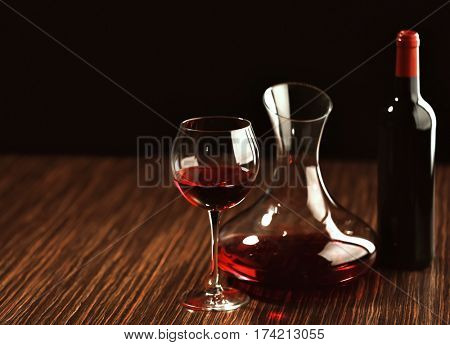 Red wine in glass, decanter and bottle on wooden table