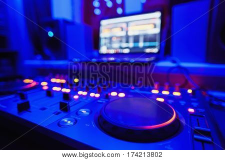 DJ console. Nout beech speakers stand on the windowsill with DJ console. Blue light and DJ console. Workplace of DJ