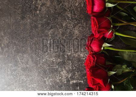 Roses lie on a dark marble table. Big beautiful bouquet of red roses. Texture colors of roses. A gift for a wedding birthday Valentine's Day roses. Space for text and design with roses. Flat lay copyspace roses.