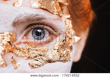 Blue eye closeup. A girl with eye an unusual make-up with gold leaf. Anonym with open eye. Masquerade Halloween. Macro photo of eye