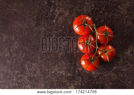 Red tomatoes lie on a dark marble table. Space for text and design and tomatoes. Flat lay copyspace tomatoes. Tomatoes on dark background