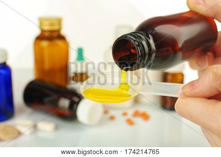 Hands pouring cough syrup into spoon on blurred background of medicines