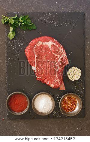 Raw fresh meat rib eye steak and seasonings on black stone slate background. Top view, blank space, vintage toned image