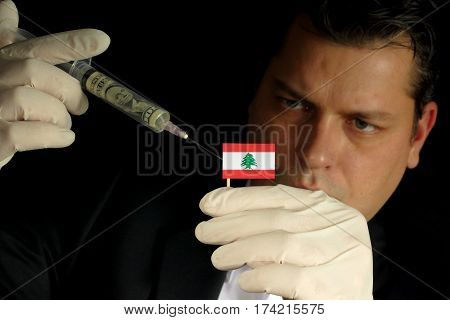 Young Businessman Gives A Financial Injection To Lebanese Flag Isolated On Black Background