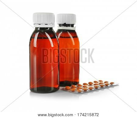 Two bottles of medicine syrup and blister pack with pills isolated on white