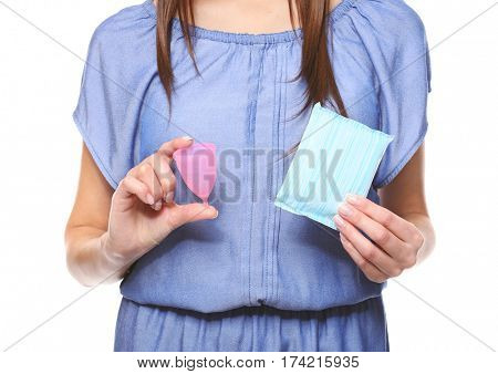Close up view of young woman making choice between menstrual cup and sanitary napkin, on white background. Gynecology concept