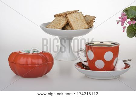 A cup of coffee French crackers and red oiler
