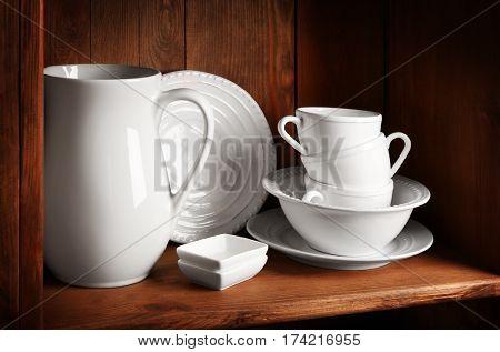 Wooden shelf with white rustic dinnerware
