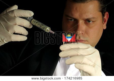 Young Businessman Gives A Financial Injection To Antigua And Barbuda Flag Isolated On Black Backgrou