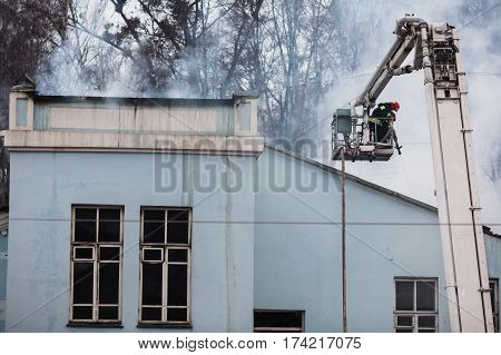 Rescuers firefighters extinguish a fire on the roof. The building after the fire. Burnt window. Ruined house. Catastrophe. Soot on the windows