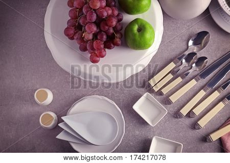 Set of rustic dinnerware with fruits on light gray table