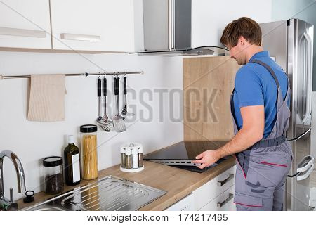 Young Man In Overall Installing Induction Stove