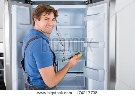 Male Technician In Overall Checking Refrigerator With Multimeter At Home