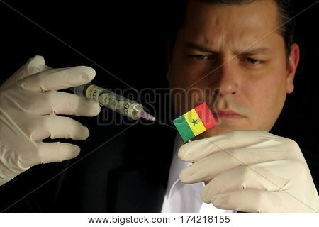 Young Businessman Gives A Financial Injection To Senegalese Flag Isolated On Black Background