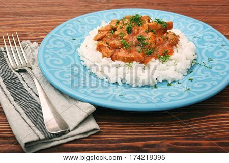 Rice with meat in tomato sause on wooden background