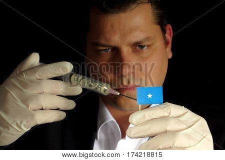 Young Businessman Gives A Financial Injection To Somalian Flag Isolated On Black Background