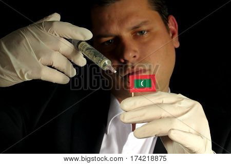 Young Businessman Gives A Financial Injection To Maldivian Flag Isolated On Black Background