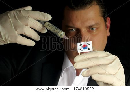 Young Businessman Gives A Financial Injection To South Korean Flag Isolated On Black Background