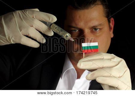 Young Businessman Gives A Financial Injection To Bulgarian Flag Isolated On Black Background