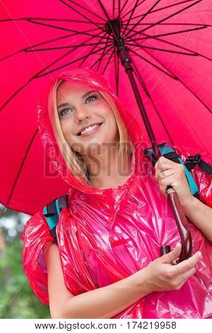 Smiling female hiker in red raincoat holding umbrella